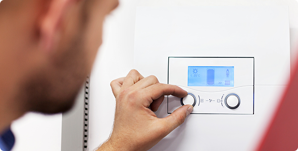 A picture of a man adjusting the thermostat on a boiler